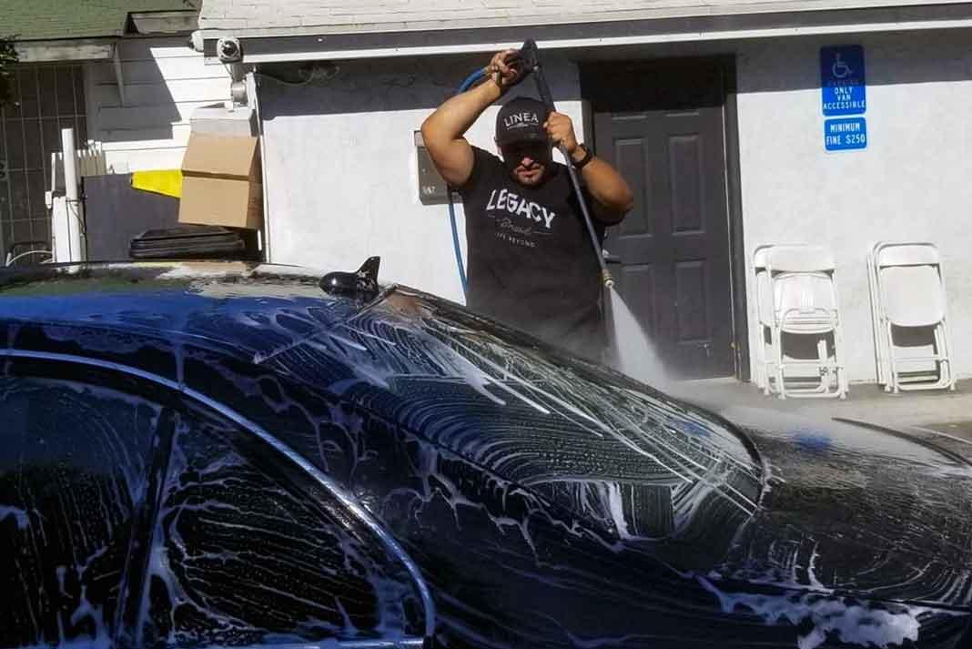 Juan Rivera le echaba ganas a la lavada con una manguera de presión