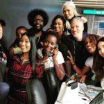 La actriz mexico-keniana Lupita Nyong'o atendiendo el teléfono entre artistas como Bruce Willis y Nicki Minaj