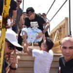 Ricky Martin pasándole el agua y los alimentos que llevaron a Nicky Jam, quien estaba arriba de uno de los camiones que repartiría la ayuda por la isla