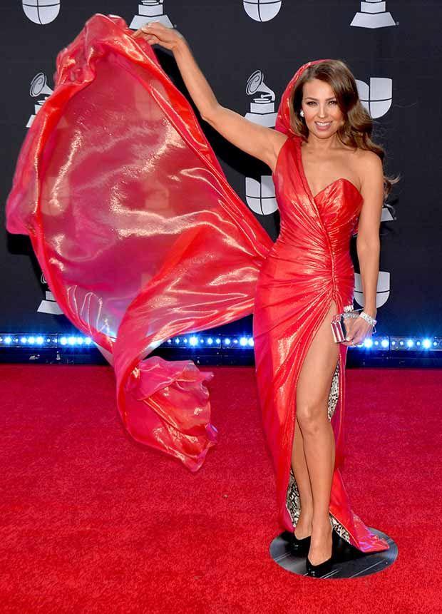Cual fusión de Caperucita Roja y Jessica Rabbit, THALÍA robó las miradas enfundada en este brilloso diseño entallado con capucha incluída.